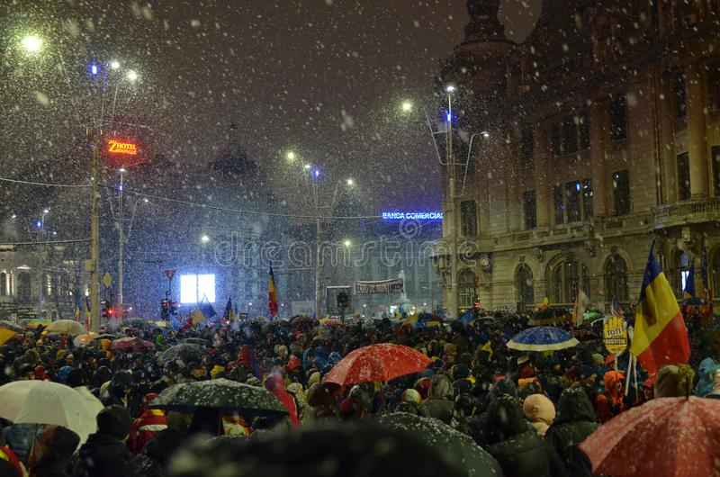 Anti government protests in Bucharest in inclement weather. Bucharest, Romania - January 20, 2018: People gathered in University Square, in the center of the royalty free stock image