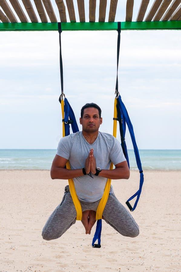 Anti--gravitation yoga, mannen som gör yoga, övar på havsbakgrunden fotografering för bildbyråer