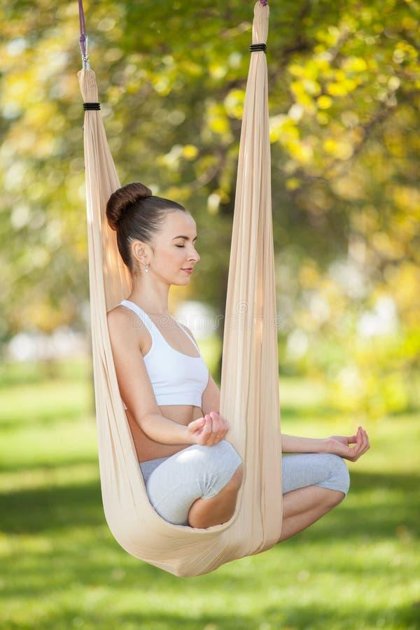Anti-gravity Yoga openlucht De gelukkige vrouw die yogaoefeningen doen, mediteert in het park Yogameditatie in hangmat Concept ge stock afbeelding