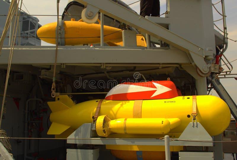 Anti-mining submersible on battleship deck. Yellow anti-mining submersible devices on docked warship deck stock photography
