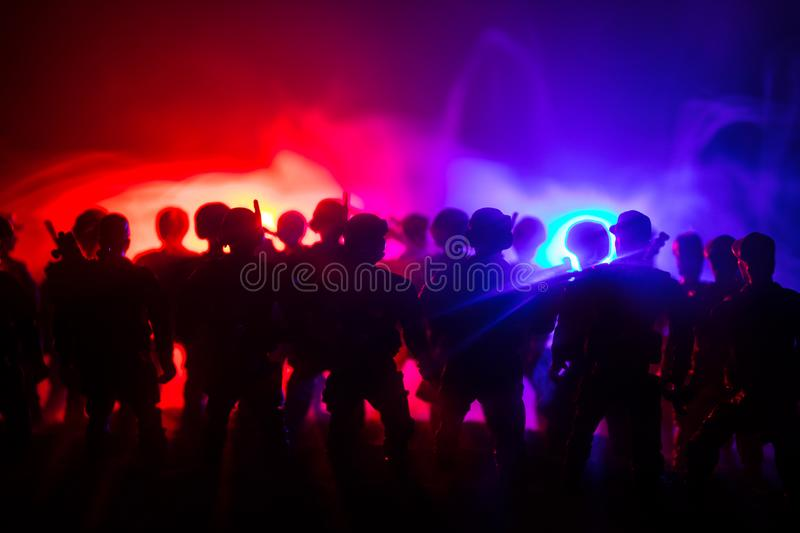 Anti-riot police give signal to be ready. Government power concept. Police in action. Smoke on a dark background with lights. Blue. Red flashing sirens royalty free stock images