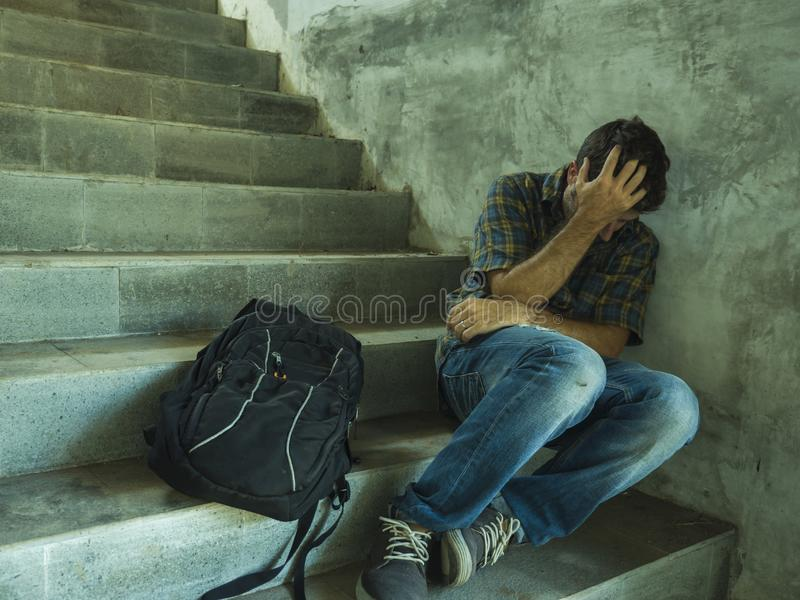 Campaign vs homophobia with young sad and depressed college student man sitting on staircase desperate victim of harassment royalty free stock images