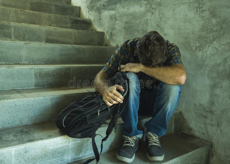 Campaign vs homophobia with young sad and depressed college student man sitting on staircase desperate victim of harassment stock photography