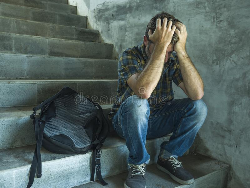 Campaign vs homophobia with young sad and depressed college student man sitting on staircase desperate victim of harassment royalty free stock image