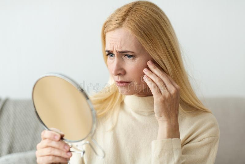 Anti--skrynkla hudomsorg Ledsen kvinna som ser i spegel royaltyfri foto
