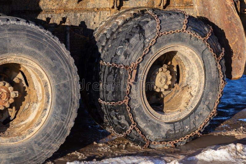 Anti--sladdning kedja på fraktlastbilhjul på vinterdagsljuscloseupen arkivbild