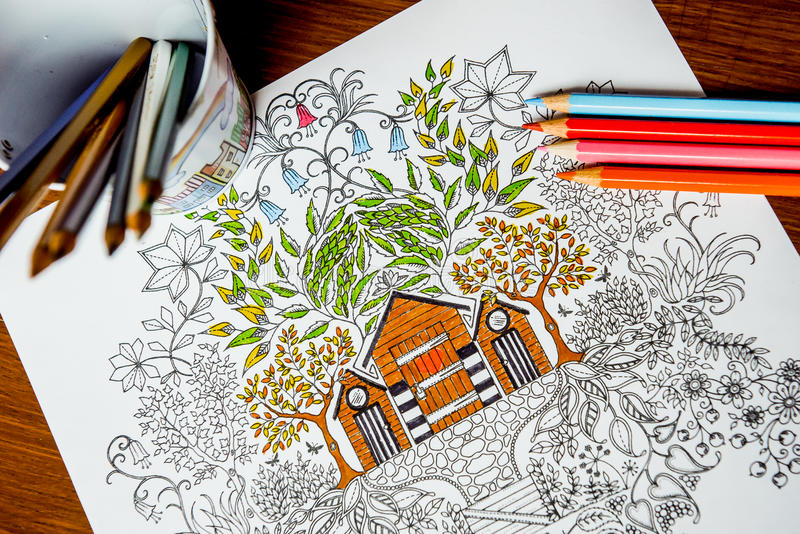 Anti-stress coloring book in the drawing process. Woman paints the razukrashki on the table are colored pencils, and tea, coffee stock illustration
