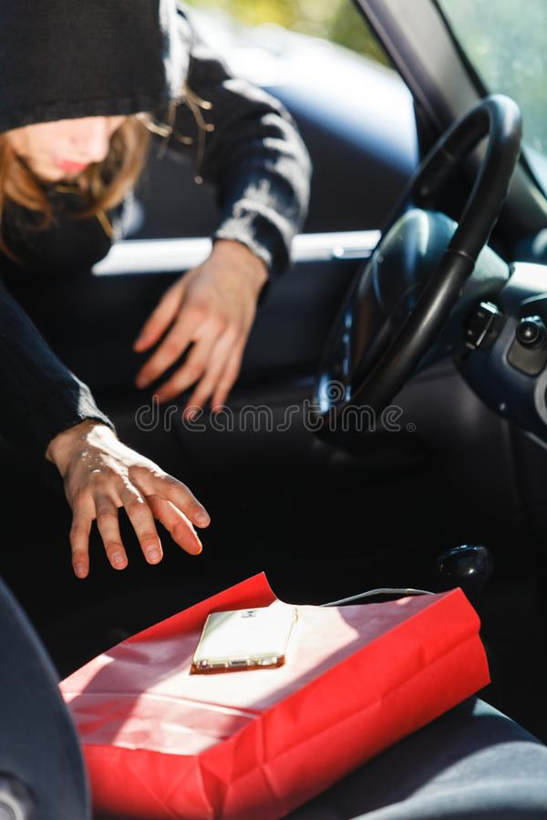 Burglar thief stealing smartphone and bag from car. Anti theft system problem concept. Burglar thief man wearing black clothes breaking into car, stealing royalty free stock images