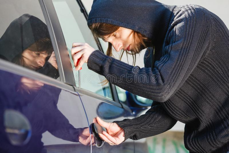 Thieft man holding screwdriver breaking into car stock photo