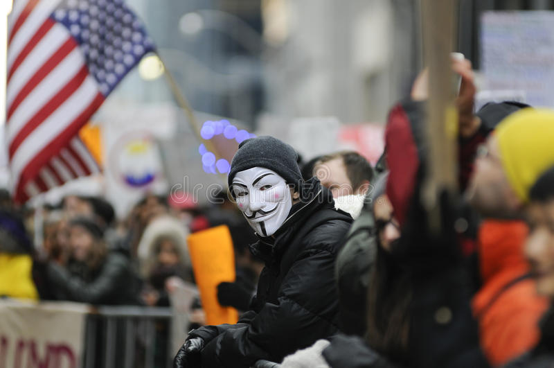 Anti Trump Rally in front of Trump Tower in Toronto. TORONTO - NOVEMBER 19: A protester wearing a `guy fawkes` mask standing among the crowd during a protest in stock images