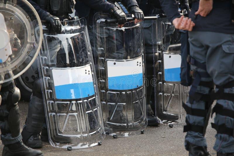 Anti--tumult poliser med sköldar under säkerhetskontroller fotografering för bildbyråer