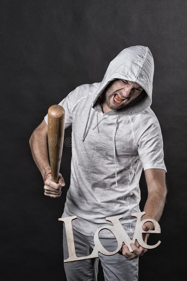 Anti valentines day. Man in hood bat love word. Angry hooligan with baseball bat. Divorce and break up. No love and hate. Concept, vintage filter royalty free stock photography