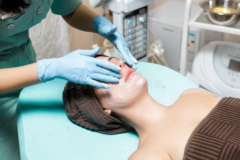 Anti-veroudert gezichtsmassage cosmetologist die massage voor jonge vrouw doen bij Kuuroordsalon royalty-vrije stock afbeelding