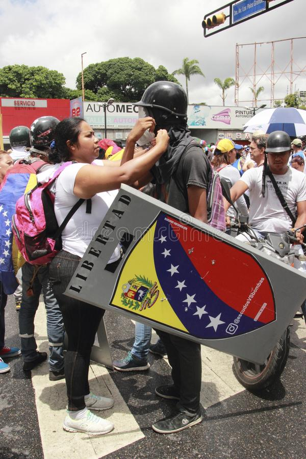 Anti vestir dos protestadores de Nicolas Maduro lança gás lacrimôgeneo a máscara durante as manifestações em massa que transforma fotos de stock royalty free