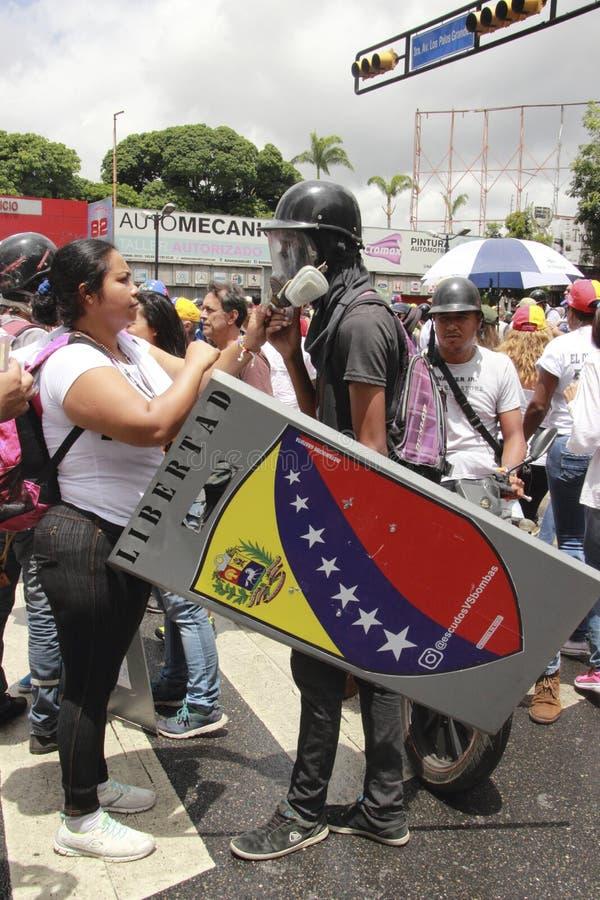 Anti vestir dos protestadores de Nicolas Maduro lança gás lacrimôgeneo a máscara durante as manifestações em massa que transforma imagens de stock