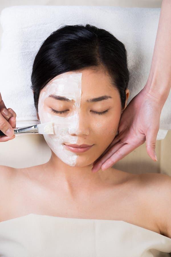 Anti-vieillissement en appliquant la crème naturelle de brosse sur le visage photo libre de droits