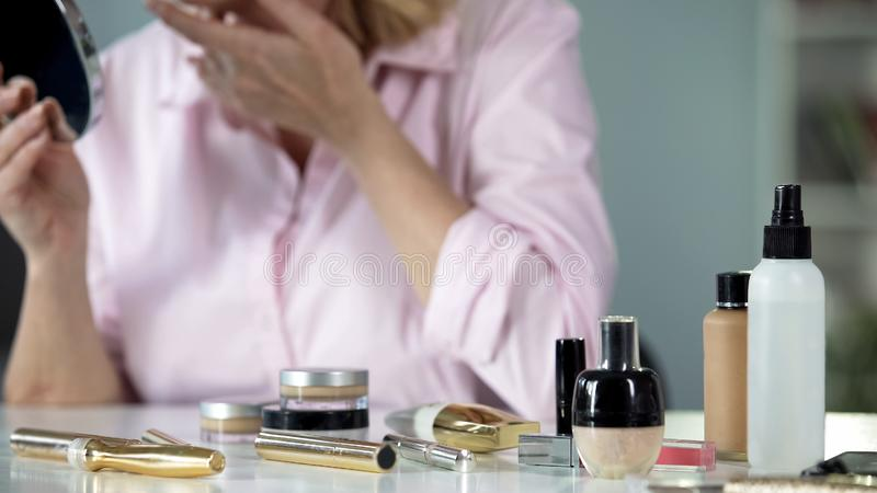 Anti-wrinkle cosmetics on table with lady on background, beauty care, aging. Stock photo stock image