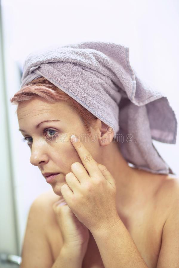 Anti-wrinkles care concept- woman is worried about the wrinkles on her face stock photography