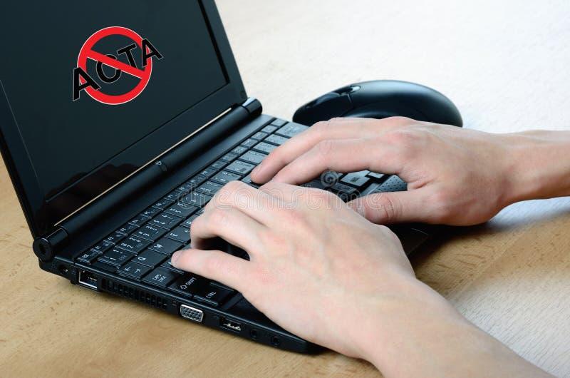 Antiactasymbol auf netbook und Händen lizenzfreie stockfotografie