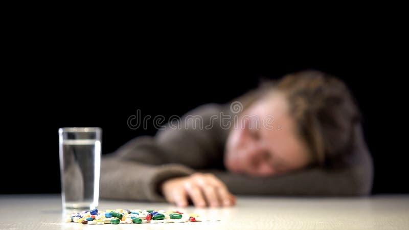 Antianxiety pigułki z wodnym szkłem na stole, żeński dosypianie na tle obrazy stock