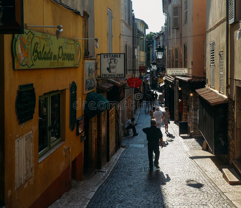 Narrow tourist street in Antibes, France. Antibes is a popular seaside town in the heart of the Cote d`Azur. Antibes, France - July 8, 2018: Narrow tourist stock photos
