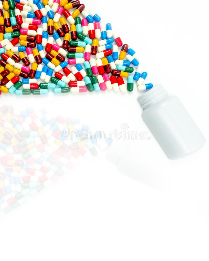 Antibiotic capsules spilling out of pill bottle royalty free stock photo