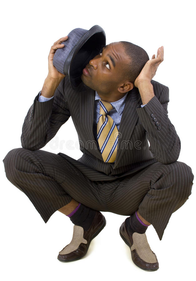 Anticipating. Young black businessman ducking from unseen threat royalty free stock images