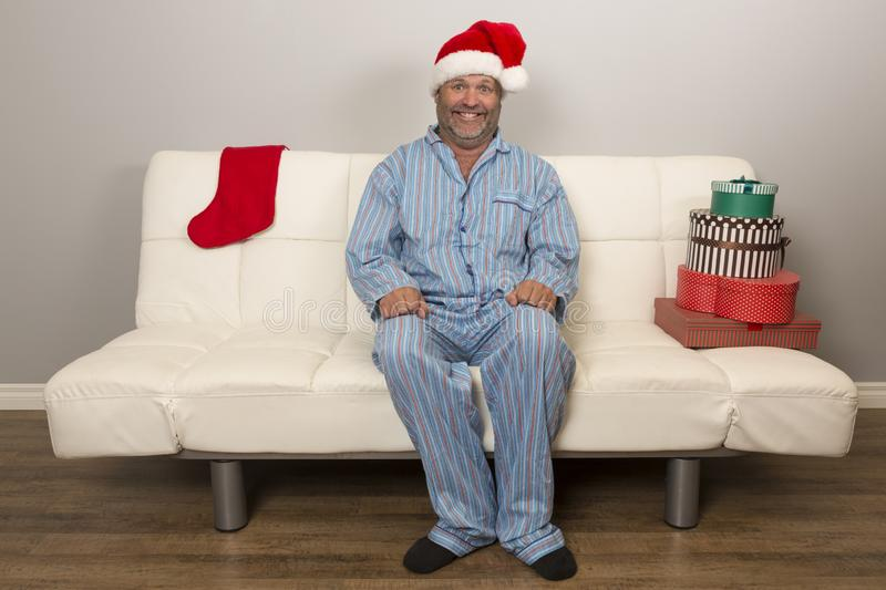 Anticipation for Festive Celebrations. A man sitting upright and excited waiting for Christmas, wearing a Santa Hat royalty free stock photos