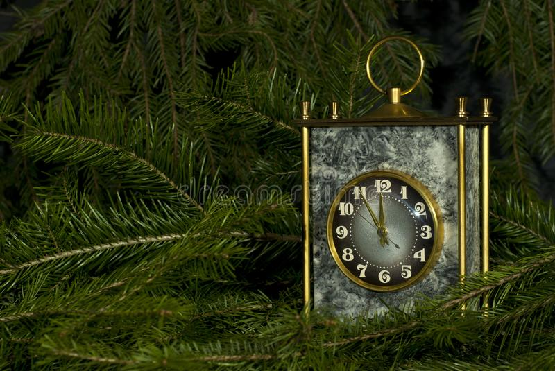 In anticipation of the holiday. Vintage desk clock in a gray stone block with brass details among the fir branches stock image