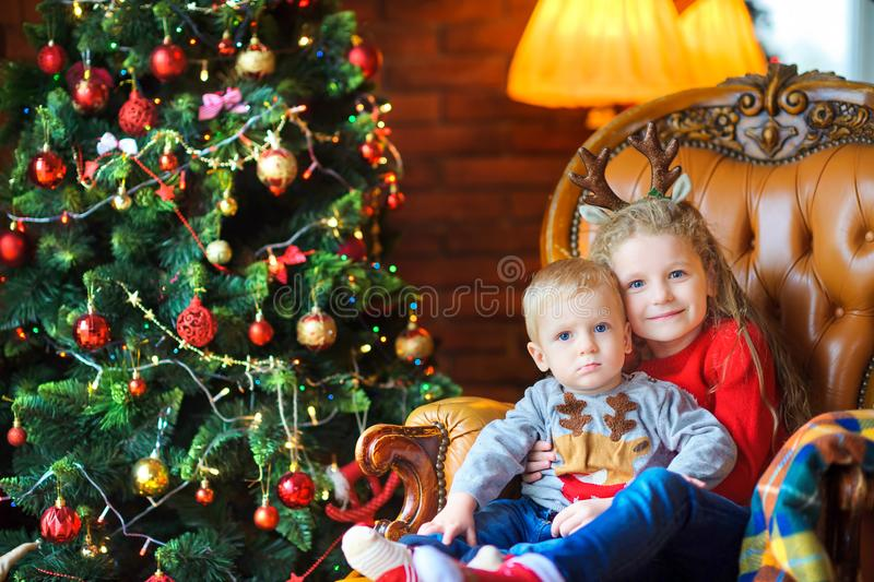 In anticipation of holidays. Sister gently hugs her little brother sitting in a chair near a festive Christmas tree stock images