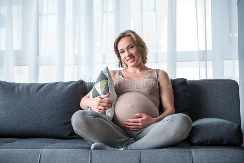 Glad expectant mother sitting on comfortable couch stock photography