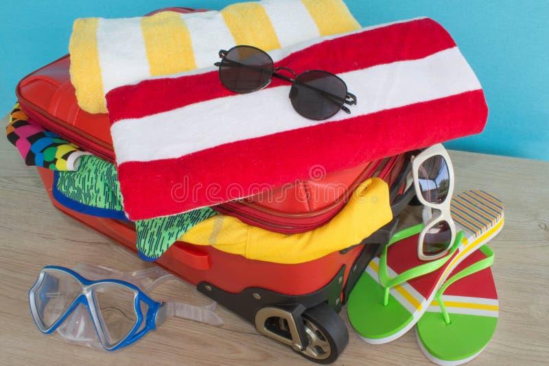 Anticipazione del viaggio Women& x27; vestiti ed accessori di s in valigia rossa fotografia stock