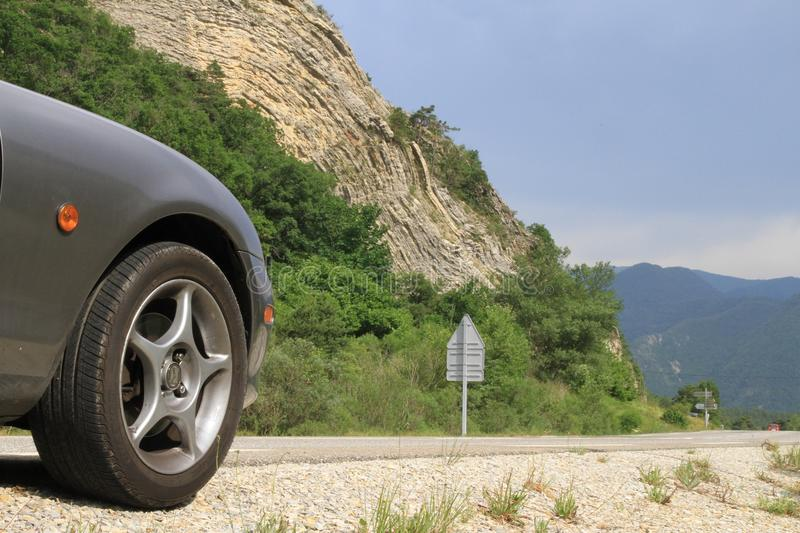 Anticline geological feature with front of Mazda MX5 in foreground. In sunshine with dark clouds behind. In the Ardeche valley Southern France royalty free stock images