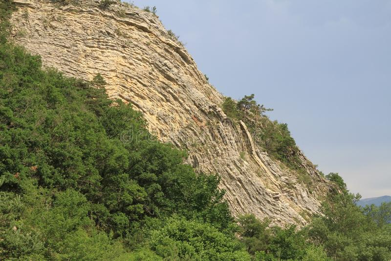 Anticline geological feature. In sunshine with dark clouds behind. In the Ardeche valley Southern France stock images