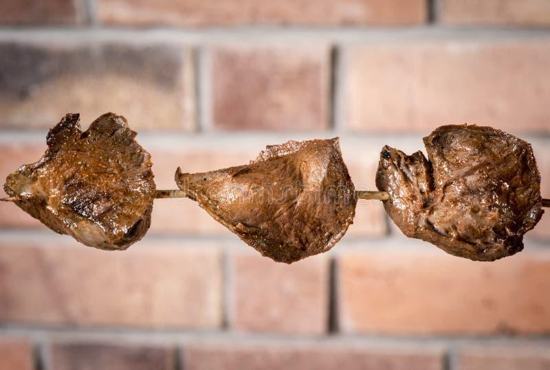 Anticuchos,秘鲁烹调,肉在格栅串起的心脏小牛肉有砖墙的背景 免版税图库摄影