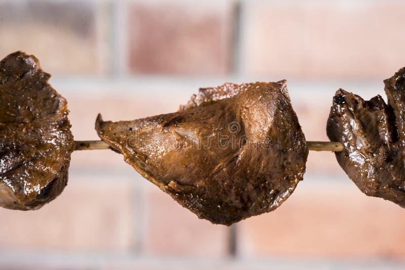 Anticuchos, перуанская кухня, телятина сердца мяса skewered на гриле с предпосылкой кирпичной стены стоковые изображения