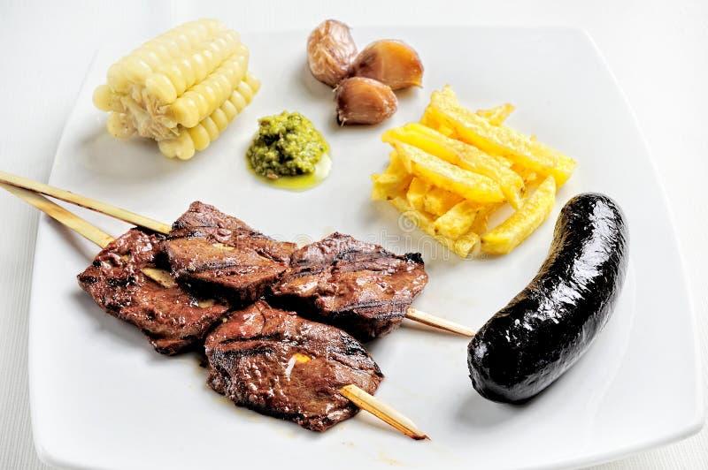 Anticuchos, cuisine péruvienne, brochettes de viande grillées de coeur de boeuf avec la pomme vapeur et maïs blanc images libres de droits
