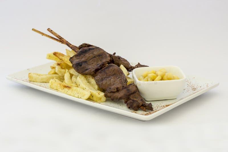 Anticuchos, cuisine péruvienne, brochettes de viande grillées de coeur de boeuf avec des pommes de terre de fritures (pommes frit photographie stock