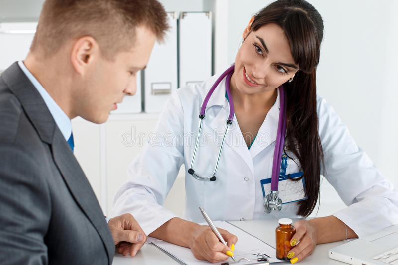 Antidepressant or man sexual potency cure. Beautiful female medicine doctor giving to male patient in business suit jar of pills. Antidepressant or men sexual stock photos