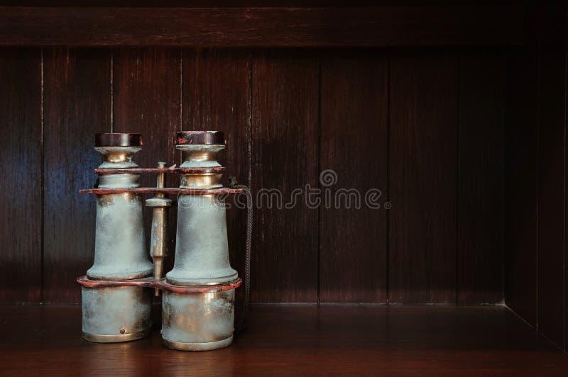 Antiek uitstekend retro messing binoculair op houten vloer donkere houten achtergrond stock foto
