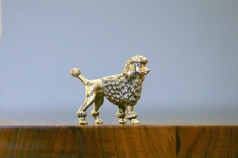 Antiek zilveren poedelstandbeeld op de houten lijst stock fotografie