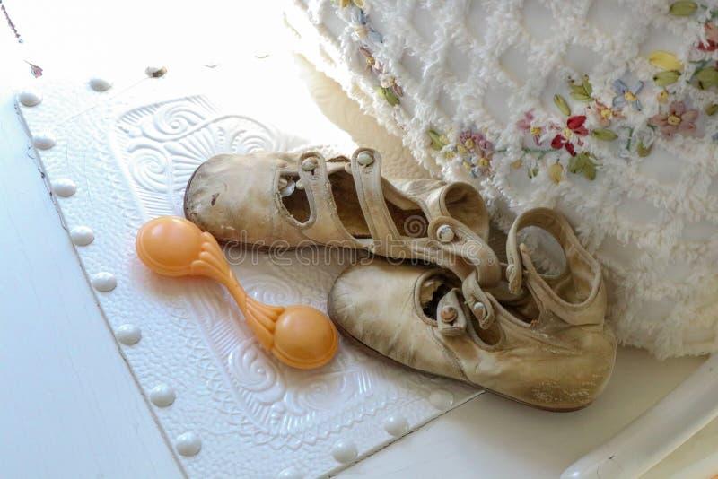 Antieke babyschoenen en rammelaar door bloemen en omzoomd hoofdkussen jpg royalty-vrije stock fotografie
