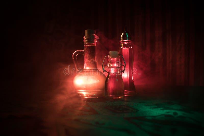 Antieke en uitstekende glasfles op donkere mistige achtergrond met licht Vergift of magisch vloeibaar concept royalty-vrije stock afbeeldingen
