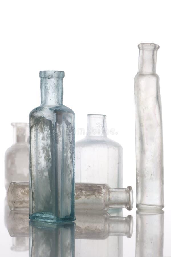 Antieke flessen op witte lijst stock fotografie