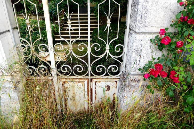 Antieke Franse tuinpoort met rode rozen royalty-vrije stock afbeeldingen