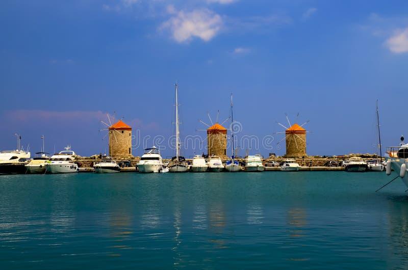 Antieke gele geeloranje molens in de haven van Mandraki, Rhodos, Griekenland royalty-vrije stock foto's