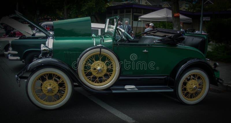 Antieke groene auto met de zetel in de laars stock afbeelding