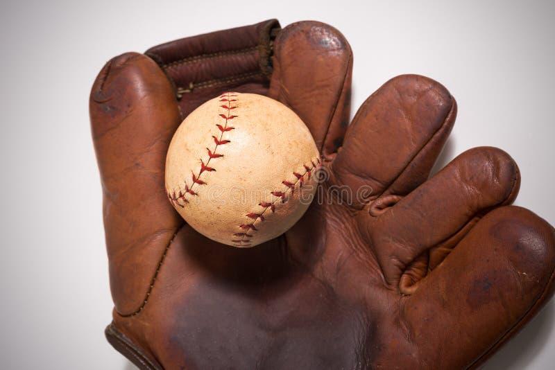 Antieke honkbalhandschoen en bal op wit stock afbeelding