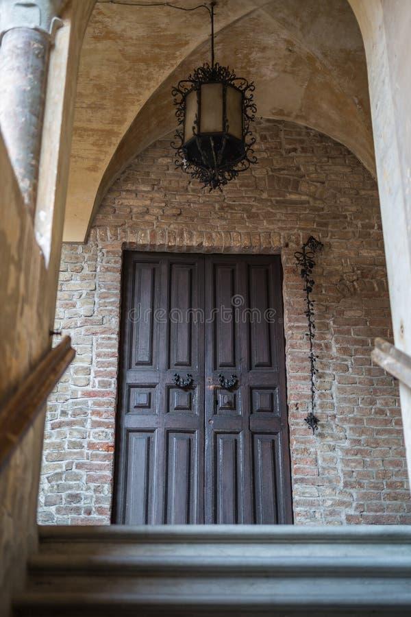 Antieke Houten Deur met Antieke Metaalkroonluchter in Fontanellato in Parma, Italië stock afbeelding