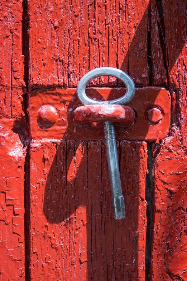 Antieke ijzersleutel van een poort op een achtergrond van oude rode houten poort royalty-vrije stock foto's